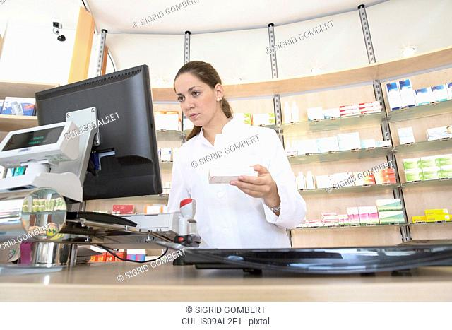 Pharmacist in pharmacy using computer