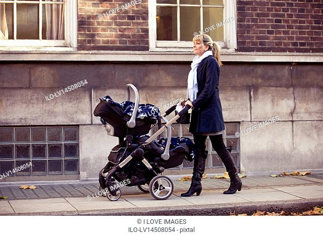 A mother pushing a double stroller in the street