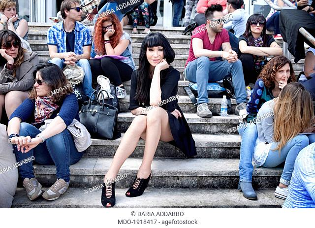 Woman sitting on the footsteps among young people. Rome (Italy), May 2014