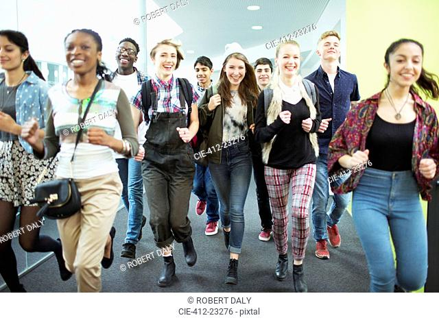 Group of cheerful students running in corridor