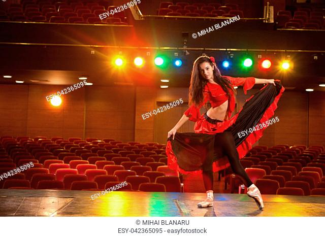 Beautiful brunette dancer, dressed in a red dress, performing a dance pose on the stage