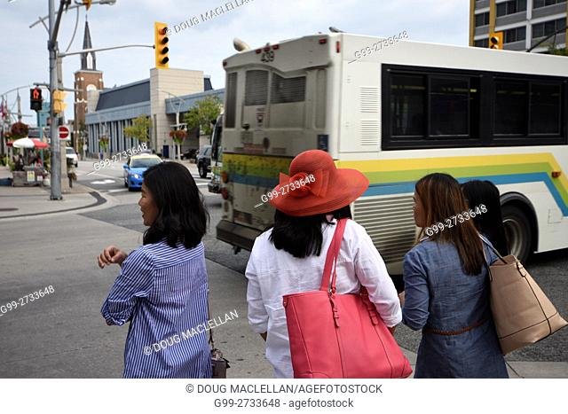 A woman with a red hat and red bag waits with three other women wait to cross at an intersection as a bus passes