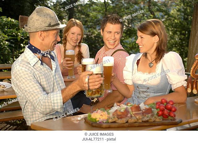 View of two young couples drinking beer, beergarden, Munich, Bavaria, Germany
