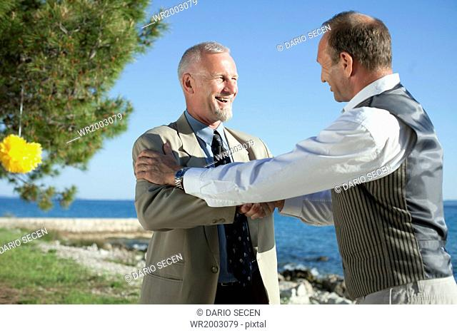 Father of the bride shaking hands with wedding guest