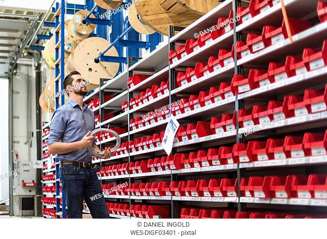 Man standing at shelf in storehouse holding cable