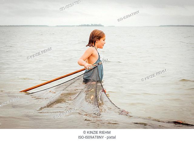 Girl learning how to use traditional fishing net, Sanibel Island, Pine Island Sound, Florida, USA