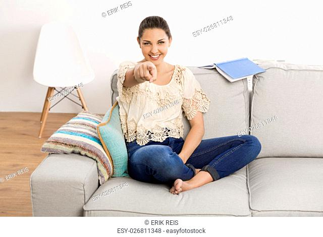Beautiful woman sitting on the couch and pointing to the camera