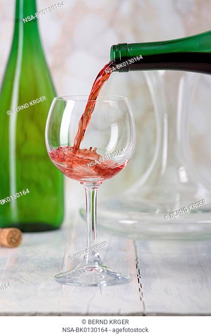 Red wine is poured from a bottle into a glass