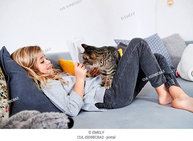Young girl lying on sofa, reading book, pet cat peering round book