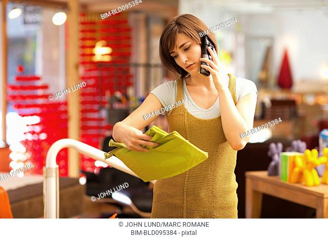 Hispanic woman shopping and using cell phone in store