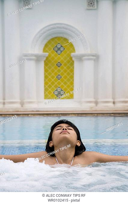 Woman in swimming pool at Dhevi Mandarin Oriental resort, Chiang Mai, Thailand