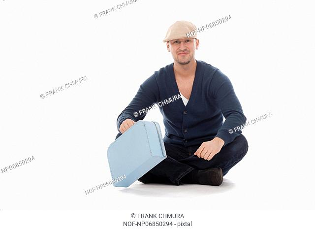 man with a cap and a toy suitcase isolated on white