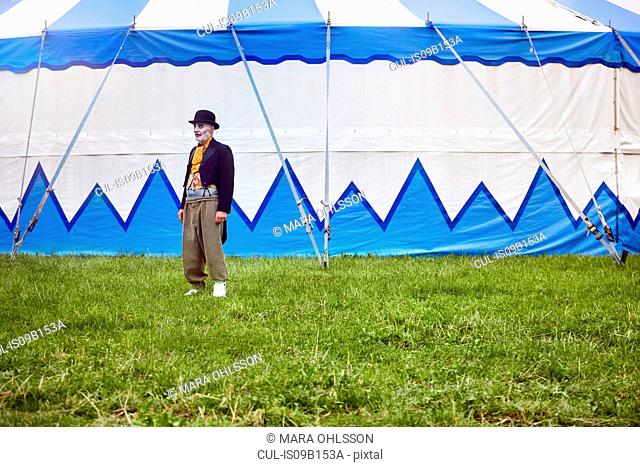 Portrait of senior male circus clown outside circus tent