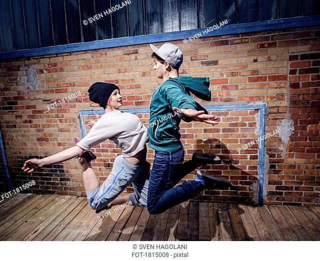 Modern dancers performing against brick wall