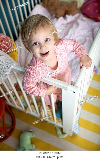 High angle portrait of female toddler in crib