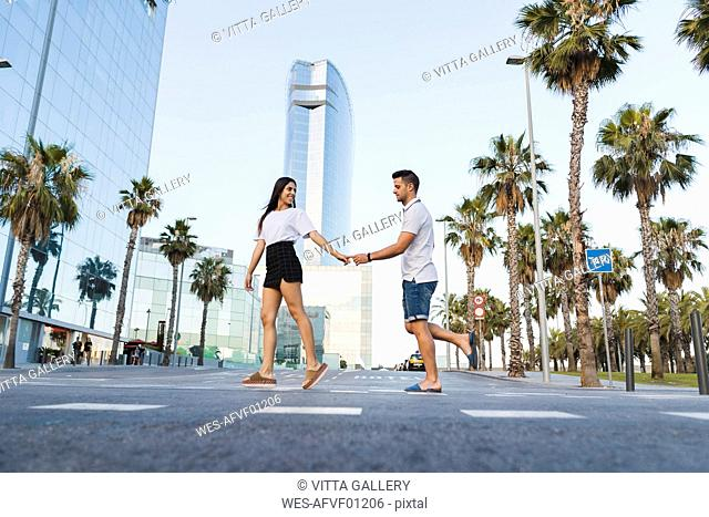 Young couple crossing street in the city, holding hands
