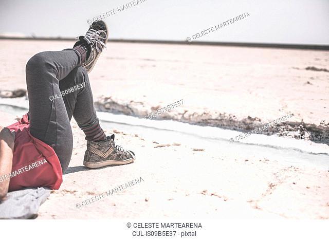 Senior woman relaxing on salt flats, low section, Jujuy, Salinas Grandes, Argentina