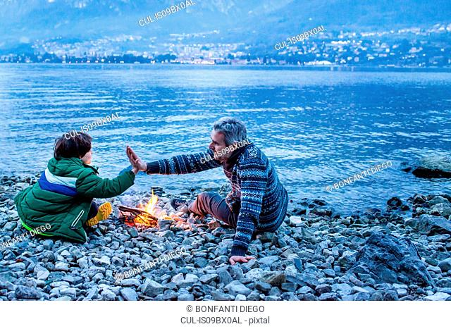 Father and son high fiving by campfire, Onno, Lombardy, Italy