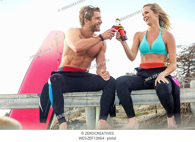Happy couple with surfboard having a drink on the beach