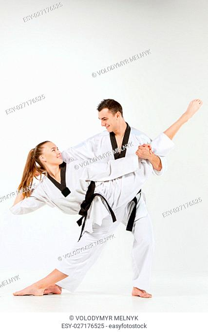The karate girl and boy in white kimono and black belt posing over gray background