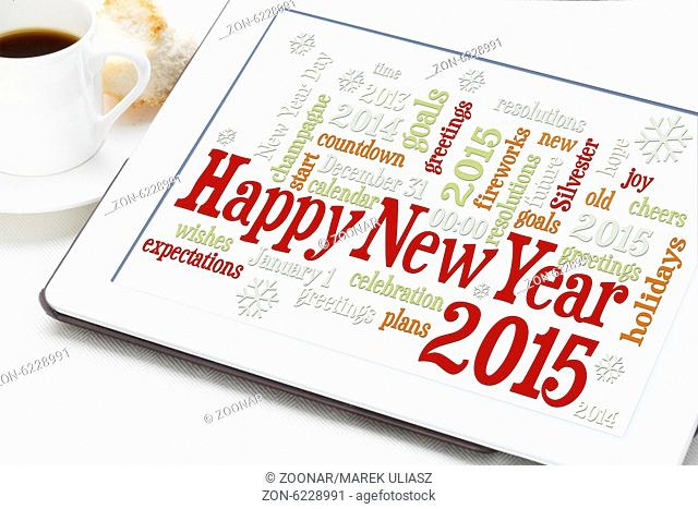 Happy New Year 2015 - word cloud on a digital tablet with a cup of coffee