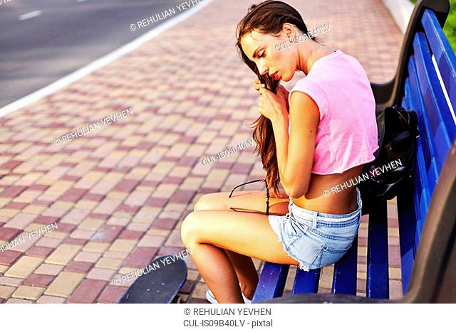 Young woman sitting on bench, fixing hair, skateboard on floor beside her
