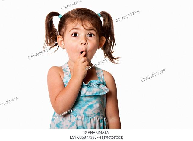 Cute surprised little toddler girl with finger in front of mouth making silence shhh gesture, isolated
