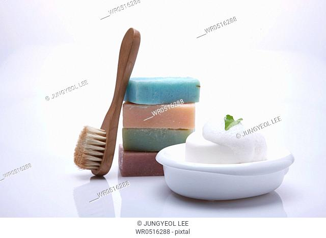 Colorful pile of soaps, bath brush and soap with foam