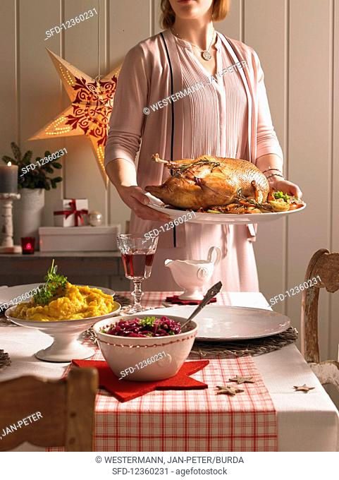A woman serving a roast goose (Christmas)