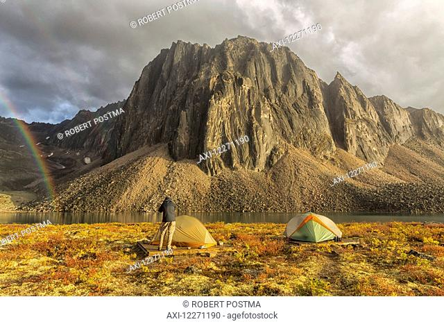 Photographer taking pictures of the late afternoon light hitting Talus Lake in the Tombstone Territorial Park of the northern Yukon; Yukon, Canada