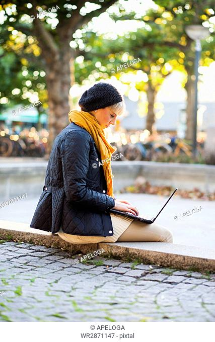 Side view of woman using laptop while sitting on retaining wall at park