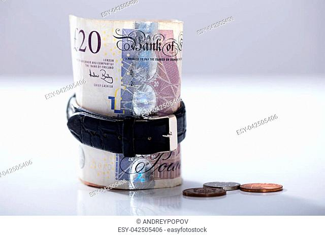 Close-up Of Rolled Up Twenty Pounds Note Inside The Wrist Watch On The Desk