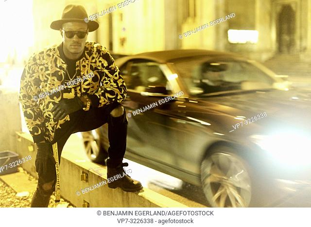 fancy blogger man at city street at night, wearing stylish outfit, blurred car, traffic, cool attitude, at Ludwigstraße in Munich, Germany