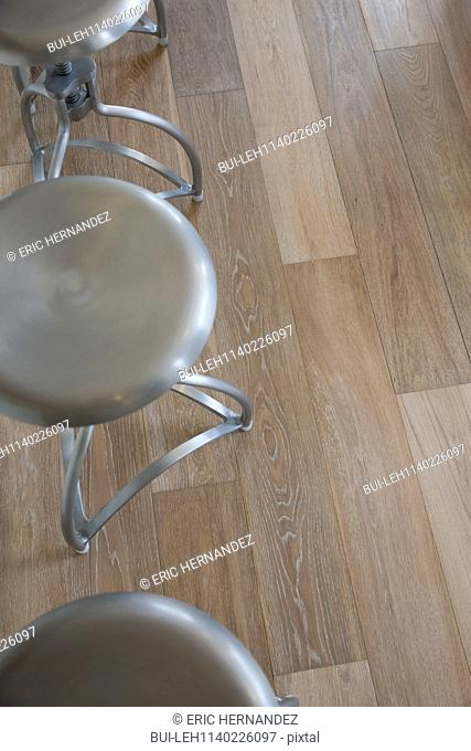 Close-up of hardwood floor with cropped stools at home