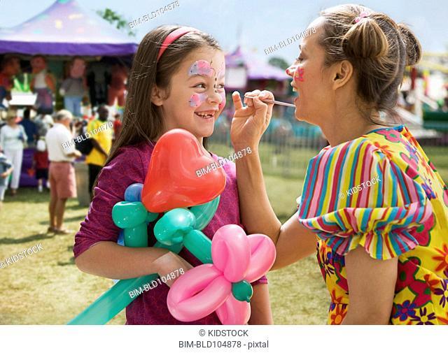 Caucasian girl having face painted at fair