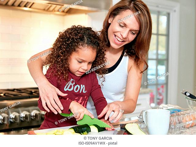 Mother helping daughter chop vegetables in kitchen