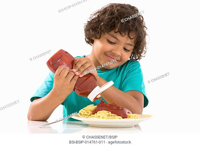 Boy eating spaghetti with ketchup