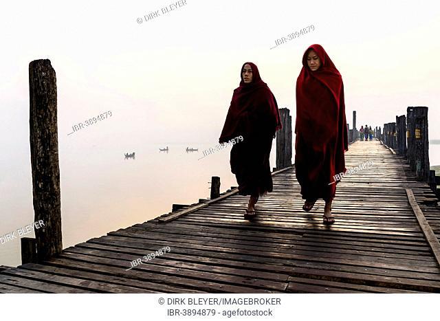 Monks walking on a teak bridge, U Bein Bridge, across Thaungthaman lake, in the morning, Amarapura, Mandalay Division, Myanmar