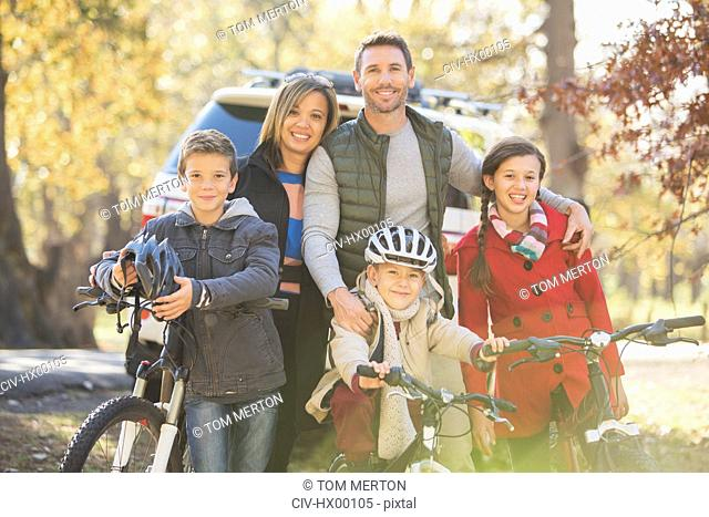Portrait smiling family with bicycles outdoors
