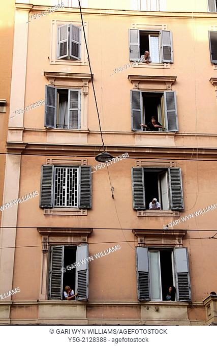 people looking out of a windows of apartments in the esquilino district in rome italy
