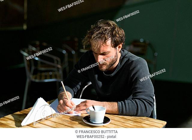 Pensive man sitting in theatre working on script