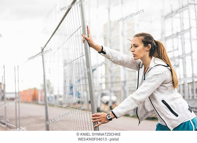 Sportive young woman standing at hoarding