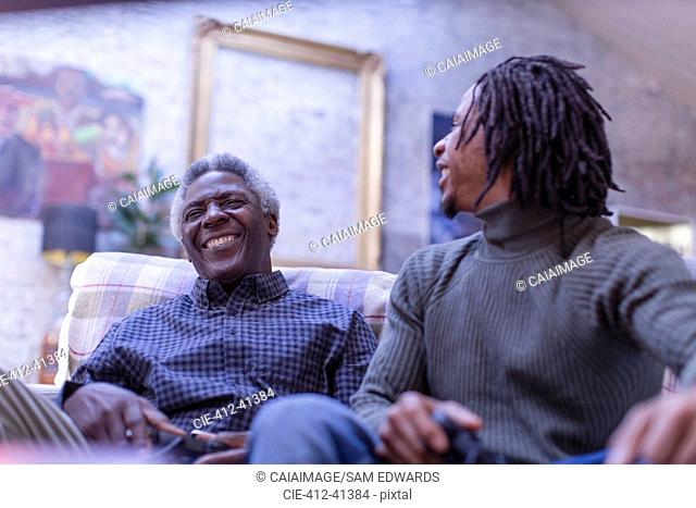 Grandfather and grandson laughing, playing video game on sofa