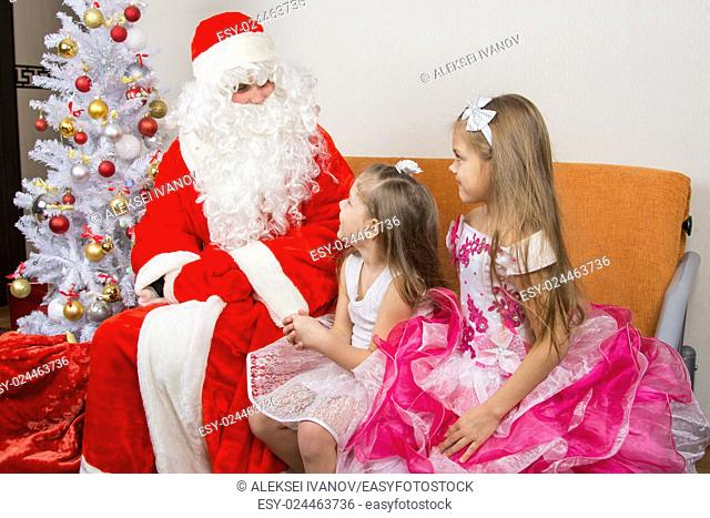 Two girls in beautiful dresses talk with Santa Claus