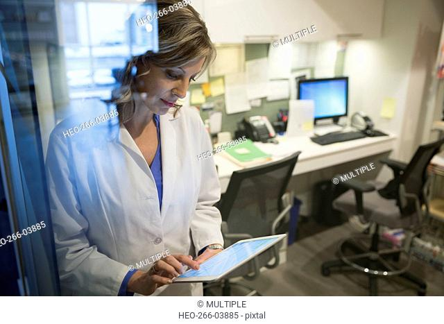 Doctor using digital tablet at nurses station
