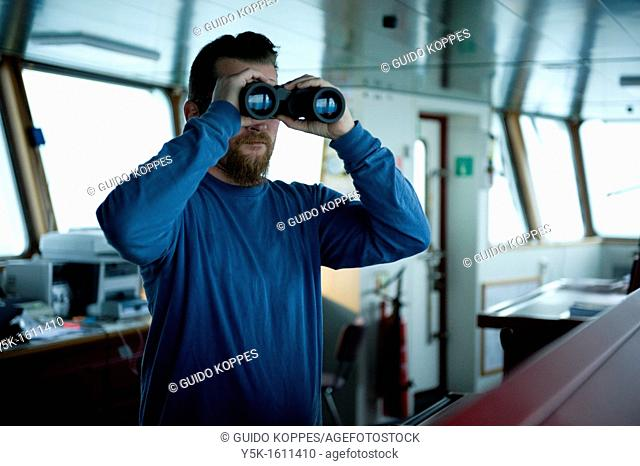 The captain of the container-vessel MV Flintercape uses binoculars to spot for other ships in the vicinity, during the voyage from Rotterdam