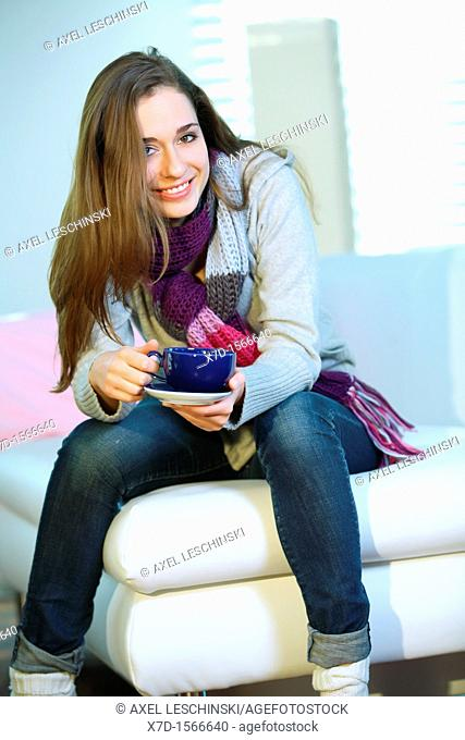 woman relaxing on sofa drinking hot beverage