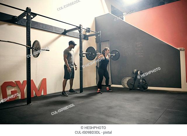 Woman in gym weightlifting using barbell