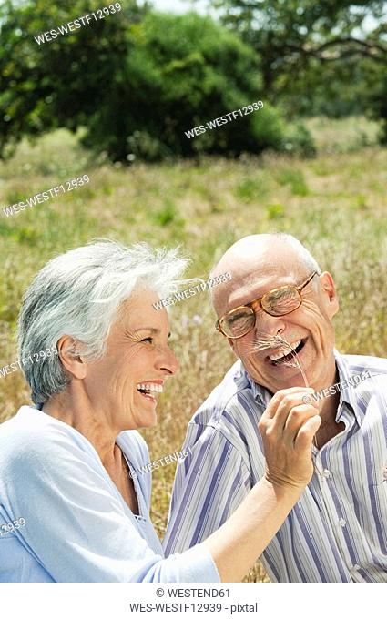 Spain, Mallorca, Senior couple sitting on grass, having fun, portrait