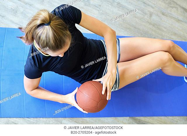 Woman doing sit-ups with ball in gym